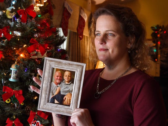 Debi Markoe of Palm Bay holds a framed photo of her late fiance, Tim Kendrick, and her son, Bear.