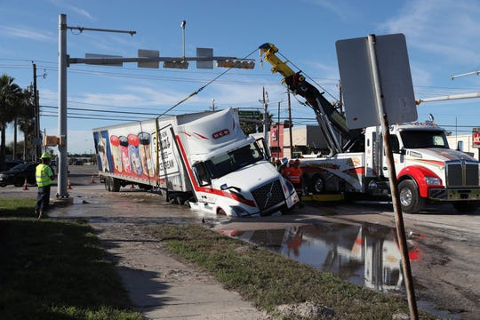 Employees with Apollo Towing service work to remove an H-E-B 18-wheeler stuck in a sinkhole at Waldron Road and Knickerbocker Street on Monday afternoon.