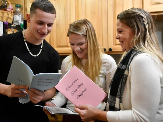 From left to right, Dylan Ben-Hayon, Alexi Hodges and Nicole Hodges look over Christmas songs during an old-fashioned caroling and cocoa event on Sunday, December 1, 2019.