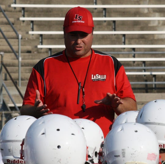 Second-year La Salle High School football coach Nate Moore addresses his team after practice Aug. 19 at La Salle. Moore went 3-7 in his first season as head coach of the Lancers in 2013.