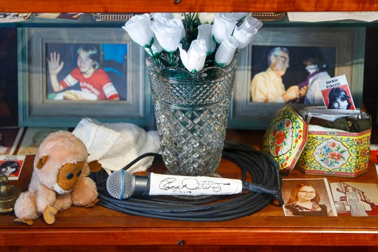 In this Thursday, Nov. 21, 2019 photo, a signed microphone by The Who's Roger Daltrey is displayed in a memorial cabinet at the Finneytown High School secondary campus in Finneytown, Ohio, along with other mementoes of the three Finneytown students killed in a stampede at the band's 1979 Cincinnati concert. Tragedy four decades ago linked the British rock band to the small suburban city in Ohio. In recent years, members of the community and the band have bonded through a project to memorialize the teens.