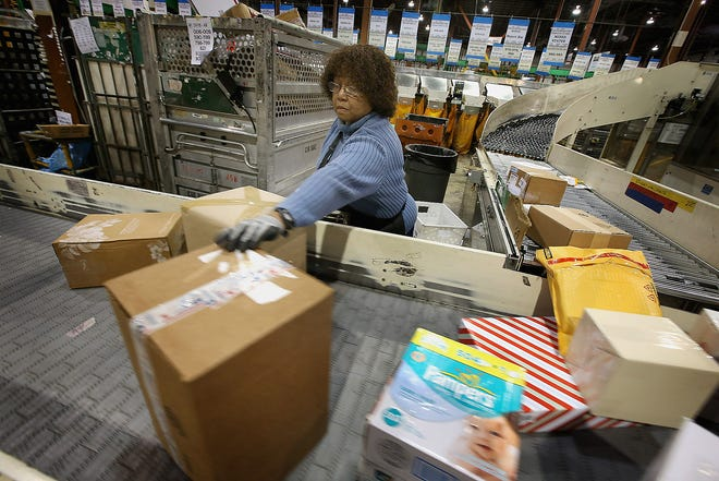 Bobbi Crump moves mail at a Postal Service center in Chicago.