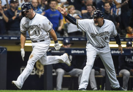 Sep 17, 2019; Milwaukee, WI, USA;  Milwaukee Brewers third baseman Mike Moustakas (11) is greeted by third base coach Ed Sedar after hitting a solo home run in the seventh inning against the San Diego Padres at Miller Park.