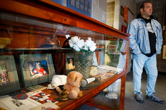In this Thursday, Nov. 21, 2019 photo, Fred Wittenbaum, of the P.E.M. scholarship that memorializes the three Finneytown students killed in a stampede at The Who's Dec. 3, 1979 concert, stands beside a cabinet of mementoes honoring the dead at the Finneytown High School secondary campus, in Finneytown, Ohio. Tragedy four decades ago linked the British rock band to the small suburban city in Ohio. In recent years, members of the community and the band have bonded through a project to memorialize the teens.