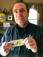 In this Nov. 25, 2019 photo, Finneytown High School alumnus John Hutchins displays a Dec. 3, 1979, concert ticket signed in 2018 by The Who's vocalist Roger Daltrey as he stands in his home near Finneytown, Ohio. Hutchins helped organize a memorial scholarship fund to honor three Finneytown students killed in a fan stampede at The Who's Cincinnati concert 40 years ago.