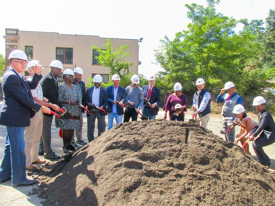 Plainfield officials and Paramount Assets executives celebrate the groundbreaking of Netherwood Flats, 70-unit luxury apartment complex featuring 4,000 square feet of ground-floor retail and underground parking.