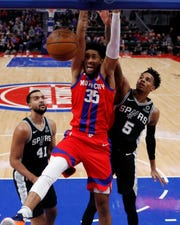 Pistons forward Christian Wood (35) dunks as Spurs guard Dejounte Murray (5) defends during the second half on Dec. 1, 2019, in Detroit.