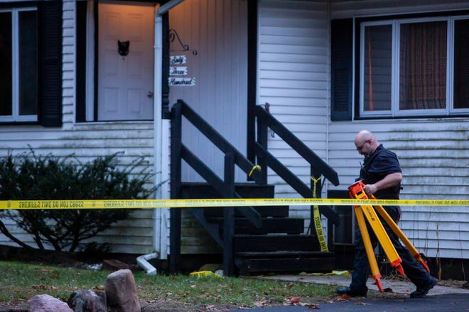An officer walks back to the crime lab after authorities say an intruder shot and wounded several law enforcement officers at a home in Comstock Township, Mich. on Monday, Dec. 2, 2019. The body of a homeowner who had been taken hostage was found inside.
