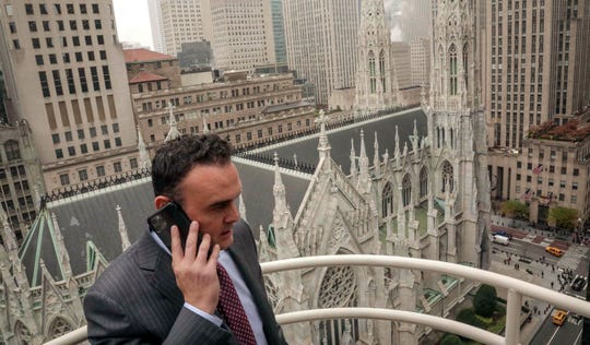 In this Tuesday, Oct. 29, 2019, photo, attorney Adam Slater takes a phone call on a patio outside his high-rise Manhattan office overlooking St. Patrick's Cathedral, in New York.