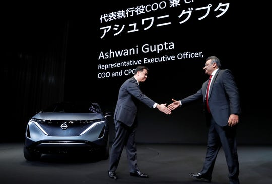 Nissan Motor's chief executive Makoto Uchida shakes hands with Nissan Motor's new COO Ashwani Gupt, next to the Ariya Concept car (L), during a news conference at Nissan Motor's headquarters in Yokohama, Japan, December 2, 2019.
