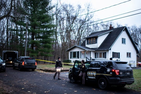 Officers talk outside a house after authorities say an intruder shot and wounded several law enforcement officers at the home in Comstock Township, Mich., on Monday, Dec. 2, 2019. The body of a homeowner who had been taken hostage was found inside.