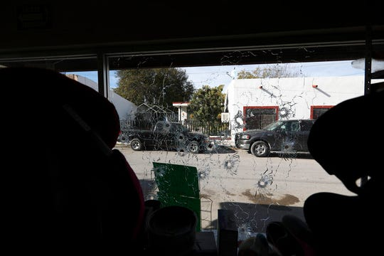 A shop's windows are riddled with bullets near City Hall after a gunbattle in Villa Union, Mexico, Monday, Dec. 2, 2019.