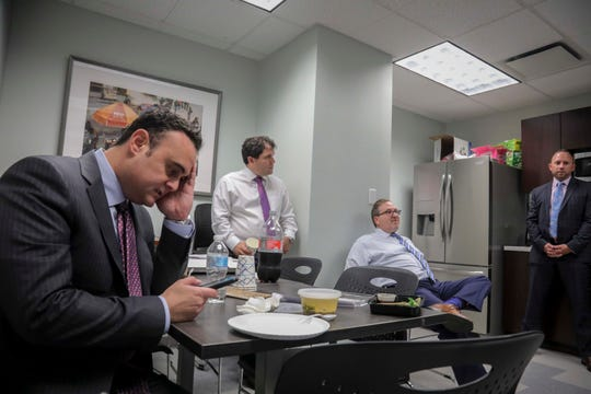 In this Tuesday, Oct. 29, 2019, photo, attorney Adam Slater, left, checks his phone during a working lunch with lawyers in his firm including partner Jonathan Schulman, second from left, Steven Alter, second from right, and Linc Leder, in Melville, N.Y.