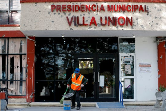 A worker cleans up outside City Hall, riddled with bullet holes, in Villa Union, Mexico, Monday, Dec. 2, 2019. The small town near the U.S.-Mexico border began cleaning up Monday even as fear persisted after 22 people were killed in a weekend gunbattle between a heavily armed drug cartel assault group and security forces.