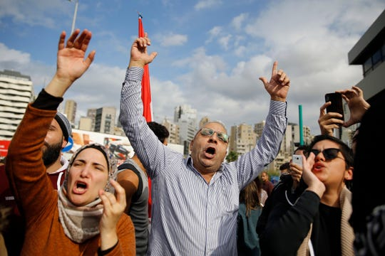Protesters chant slogans during ongoing protests against the Lebanese political class, in front of a Finance Ministry building in Beirut, Lebanon, Friday, Nov. 29, 2019.