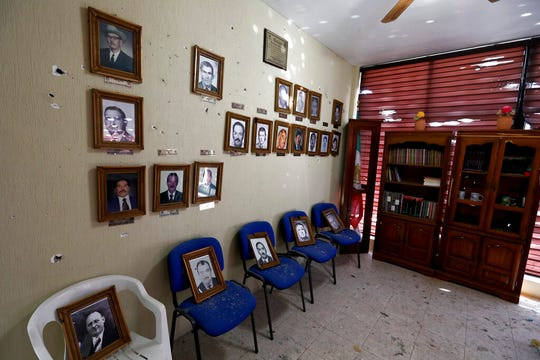 Portraits of former mayors of Villa Union hang on a wall riddled with bullet holes after a gunbattle, inside City Hall, in Villa Union, Mexico, Monday, Dec. 2, 2019.