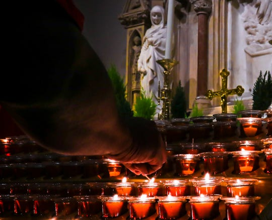 In this Wednesday, Nov. 27, 2019, photo, a Catholic faithful lights candles at a prayer station during a visit to one of the great symbols of the Roman Catholic Church, St. Patrick's Cathedral, in New York.
