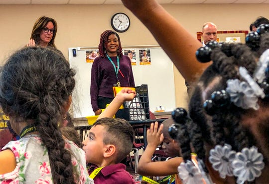 """Cammiel """"Ms. Camm"""" Canady looks on Monday, Dec. 2, 2019, as her students tell another teacher what they ate for Thanksgiving dinner. She is the first recipient of the Lee County school district's """"Grow Your Own Teacher Scholarship Program"""" and now teaches at Sunshine Elementary School in Lehigh Acres. The scholarship program, which is being expanded, helps high school seniors, or college-level students who want to change their majors, become teachers."""