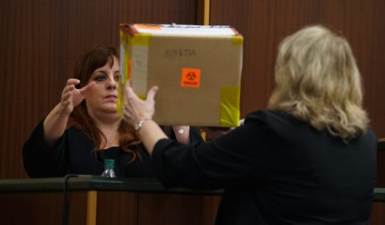 FBI forensics examiner Linda Otterstatter inspects an evidence box during her expert witness testimony. The trial for Mark Sievers, who is charged with first-degree murder and conspiracy to commit murder for the death of his wife Teresa Sievers, continued Monday, Dec. 2, 2019, at the Lee County Justice Center in Fort Myers.
