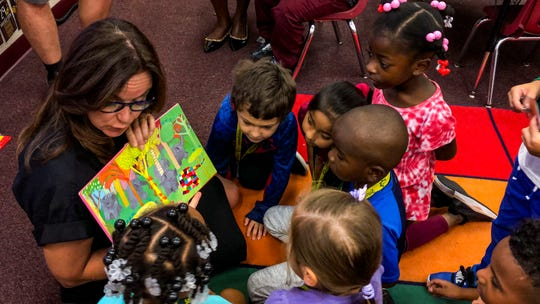 """State Sen. Lizbeth Benacquisto, R-Fort Myers, reads to a few of the kindergarten students in Cammiel Canady's class at Sunshine Elementary School. Canady is the first recipient of the Lee County school district's """"Grow Your Own Teacher Scholarship Program"""" to join the classroom and was highlighted in a news conference Monday, Dec. 2, 2019, announcing an expansion of the scholarship with new state funds."""