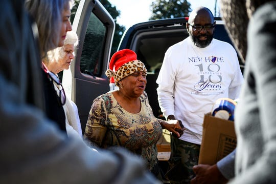 "Janice ""Pinky"" Whitner and Deacon Michael Lee Leaphart lead a prayer before storing food donations for the homeless Wednesday, Nov. 20, 2019."