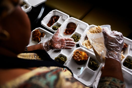 """Janice """"Pinky"""" Whitner fills containers with home-cooked food to hand out to the homeless Wednesday, Nov. 20, 2019."""