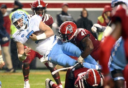 North Carolina Tar Heels quarterback Sam Howell (7) dives forward as he is tackled by North Carolina State Wolfpack linebacker Isaiah Moore (41) during the first half at Carter-Finley Stadium, Nov 30, 2019.