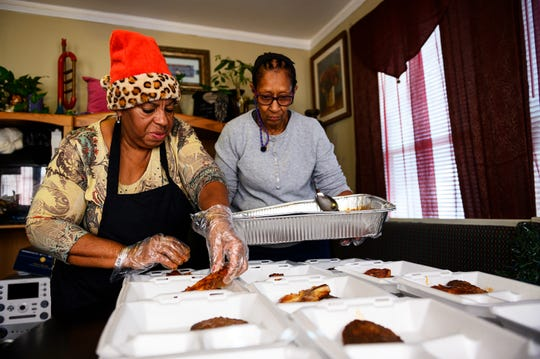 "Janice ""Pinky"" Whitner and Delores Young fill containers with home-cooked food to hand out to the homeless Wednesday, Nov. 20, 2019."