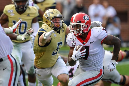 Georgia Bulldogs running back D'Andre Swift (7) is hit by Georgia Tech Yellow Jackets linebacker David Curry (6) and fumbles the ball during the second half at Bobby Dodd Stadium, Nov 30, 2019.