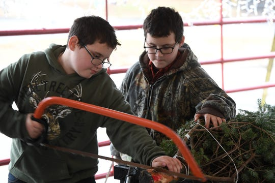 Brothers Leland Majors, left, and Caydin Majors saw the end off of a customer's tree at the annual Henderson Boy Scouts Troop 301 Christmas tree fundraising sale on Green Street Saturday.