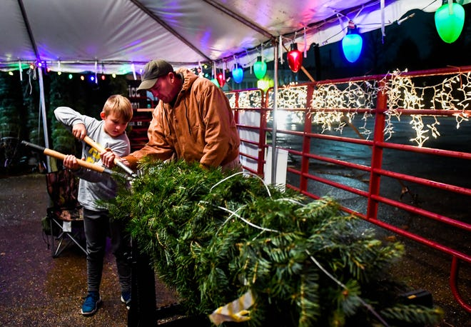 Dru Wall helps his son, Grant Wall, cut the bottom branches off a tree at the annual Henderson Boy Scouts Troop 301 Christmas tree fundraising sale on Green Street Saturday.