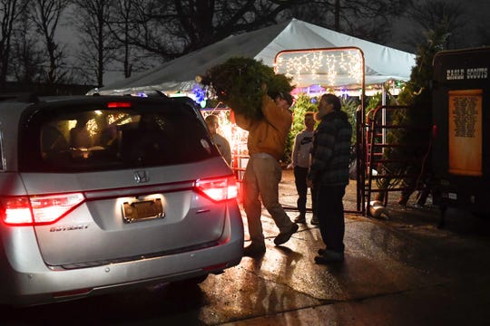 Boy Scout parent Dru Wall loads a customer's tree on their van at the annual Henderson Boy Scouts Troop 301 Christmas tree fundraising sale on Green Street Saturday.