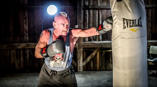 Seventy-year-old U.S. military veteran Al Hughes, Jr., works the heavy bag in the 200-year-old barn he uses to train on his family's property in Parker City.