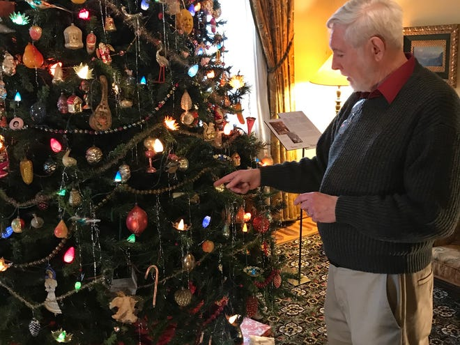 Curator George Johnson explains the details of the presidential Christmas tree in the living room of the Decorative Arts Center. The tree represents what a tree from the 1920s during President Warren Harding's term in office would have looked like.