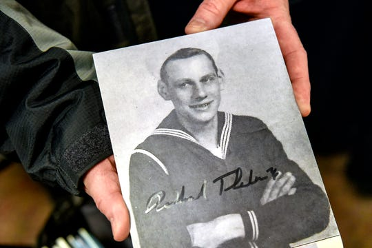 A photo of World War II veteran Dick Thelen as a young sailor was passed around during a ceremony honoring Thelen on Monday, Dec. 2, 2019, at Grace Lutheran Church in Lansing. Thelen is the last Michigan survivor of the sinking of the USS Indianapolis.