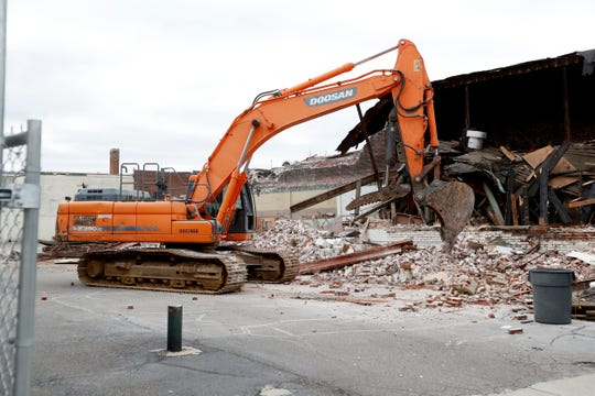 Demolition crews work to bring down a building Monday, Dec. 2, 2019, on Union Row near South Fourth Street in Memphis.
