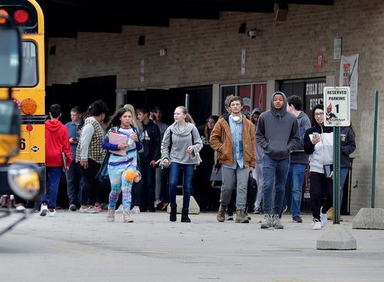 Waukesha South High School students leave the building after they were dismissed early after police say a 17-year-old student was shot after he pointed a gun at officers inside the school, Monday, Dec. 2.