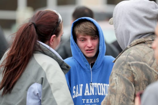 Ryan Hamilton, a 16-year-old junior, talks with his mother, Sara Hamilton, and father, Ryan Pike, Monday outside Waukesha South High School. A student was shot by police after he pointed a pellet gun at police, Police Chief Russell Jack said.