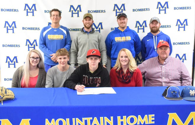 Mountain Home pitcher Trey Jordan (front, center) signed Monday to play baseball at Allen Community College in Iola, Kan. Pictured with Jordan are: (front row, from left) his sister Blakely Wilson, his brother Trent Jordan, his mother Brandy Jordan, his father Tom Jordan; (back row) MHHS assistant Phillip Taylor, MHHS head baseball coach Tim Carver, MHHS assistant Kyle Stephens, and MHHS assistant Blake Hendricks.