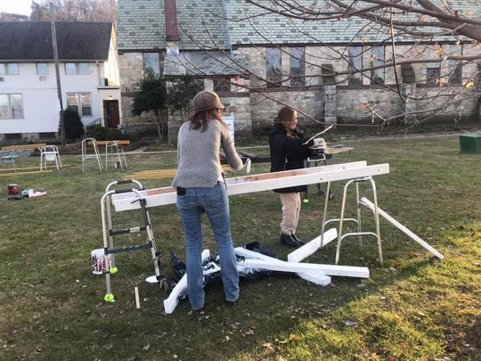 Dover residents paint plywood pieces for the floats on display at Friday's holiday parade.