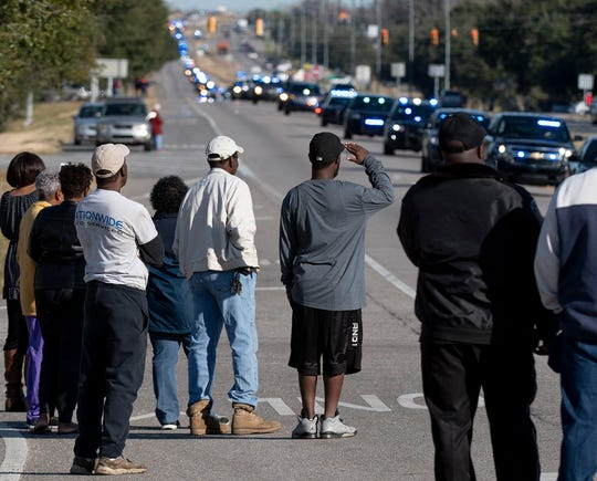 People line the road as the funeral procession of Lowndes County Sheriff Big John Williams makes its way along highway 80 in Montgomery, Ala., on Monday, December 2, 2019.