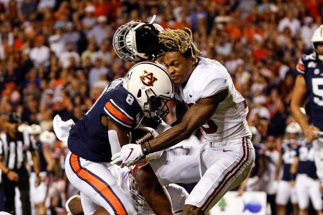 Auburn running back Shaun Shivers (8) runs into Alabama defensive back Xavier McKinney (15) and knocks his helmet off during a touchdown run in the Iron Bowl on Saturday, Nov. 30, 2019, in Auburn, Ala.