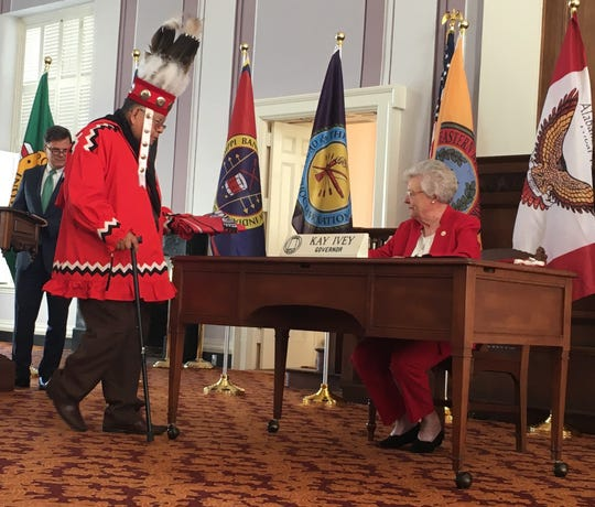 Herbert Johnson Sr. of the Alabama-Coushatta Tribe of Texas exchanges flags Monday with Gov. Kay Ivey.