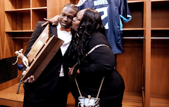 The Tennessee Titans Mr. Football winner James Moore of Stratford High is congratulated by his mother, Charron, in the Titans' locker room on Monday, Dec. 2, 2019 at Nissan Stadium in Nashville.