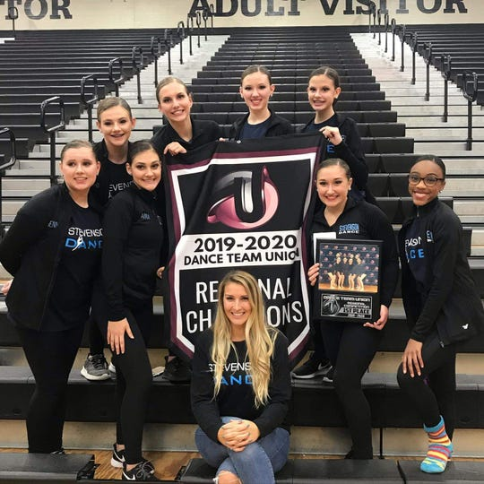 Coach Amy Prochazka, Vivienne Zieman, Anna Bodescu, Taylor Arceri, Nyla Meekins, Maggie Weikert, Evelyn Shymanski, Sydney Stolar and Ava Barber celebrate Livonia Stevenson's first-place win at the Dance Team Union's regional competition.