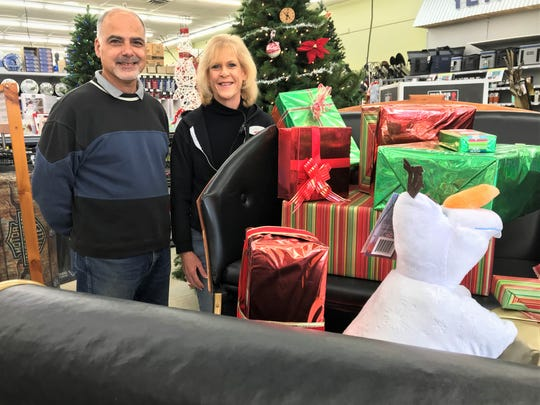 Salem Township resident Joe Grima stands with Cindy Heins, the assistant store manager at Great Lakes Ace Hardware in South Lyon, in front of a sleigh owned by Grima. The sleigh used to be featured at Hudson's department store in downtown Detroit and is on display this month at the hardware store on Pontiac Trail.