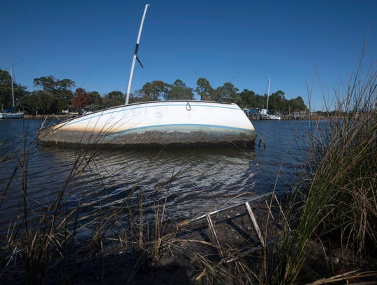 A sailboat that appears to have run aground rests in Bayou Chico on Monday.