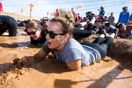 Participants crawl through a mud pit in Tough Mudder Arizona 2018.