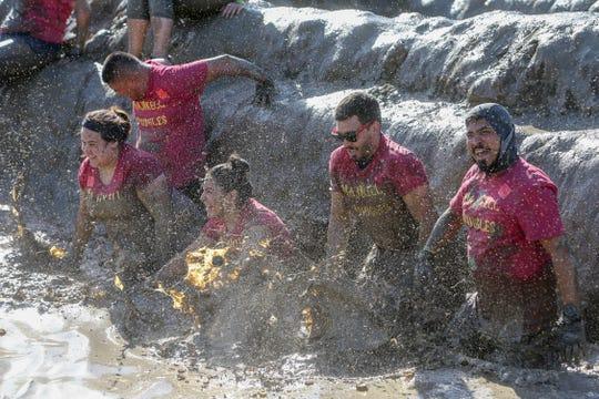 A team wades through mud in a Tough Mudder obstacle.