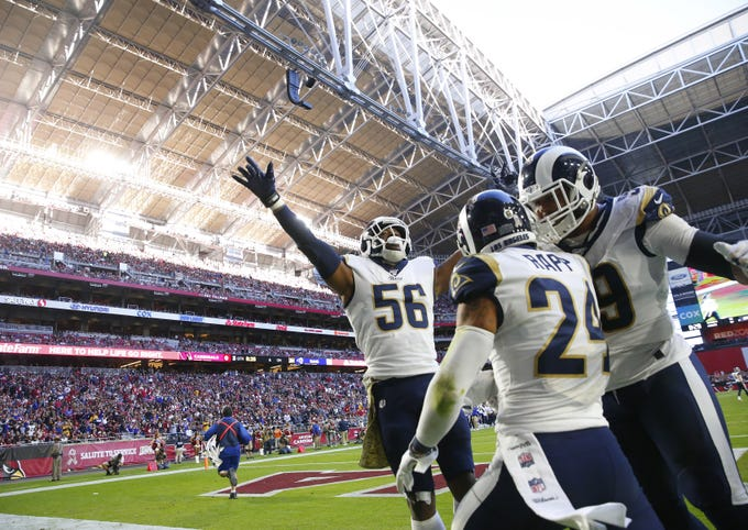 Los Angeles Rams safety Taylor Rapp (24) celebrates with defensive end Dante Fowler (56) and Sebastian Joseph-Day (69) after returning an interception for a touchdown against the Arizona Cardinals during the third quarter at State Farm Stadium December 1, 2019.
